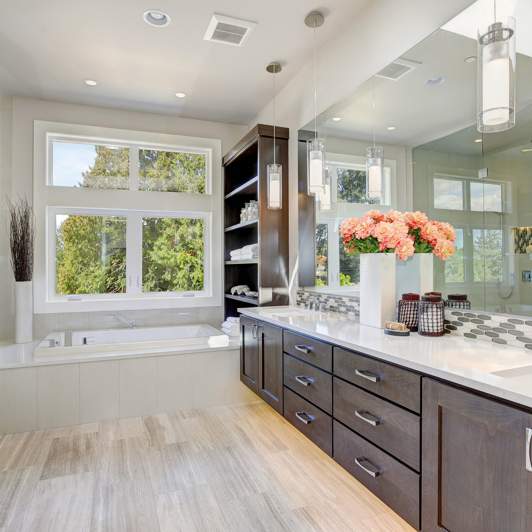 Contemporary master bathroom features a dark dual vanity cabinet glass walk-in shower drop-in tub and open cabinets filled with shelves. Northwest USA